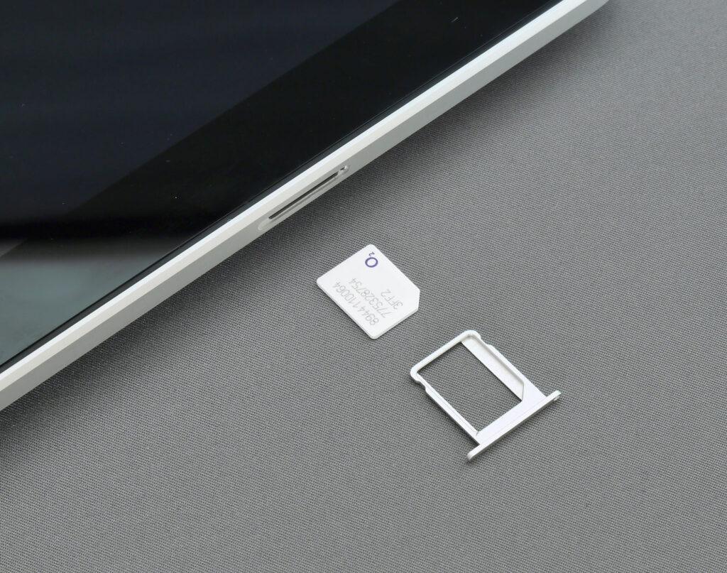 Une carte sim à côté d'un smartphone